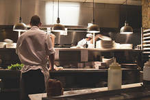 Professional clean kitchen with a chef preparing something